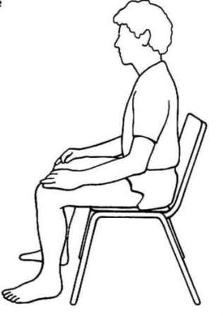 Meditating sitting in a chair. Feet flat on the floor. Hands resting on thighs. Back straight.