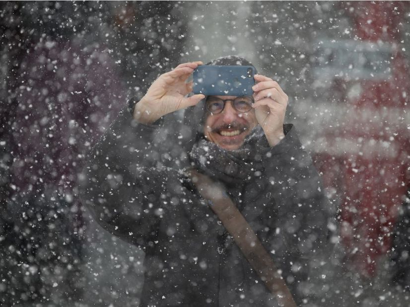 Quebec filmmaker Philippe Falardeau takes pictures of a snow squall in Old Montreal on Tuesday.